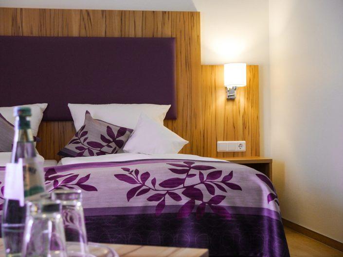 Hotelzimmer Lila Bett Kissen Decke Wasserflasche Gläser