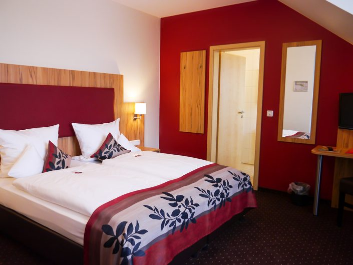 Hotelzimmer Rot Bett Badezimmer Kissen Tür Spiegel Decke