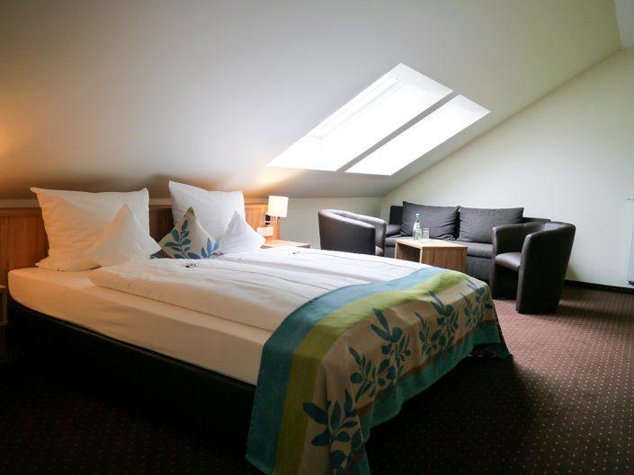 Hotelzimmer Grün Bett Sitzecke Fenster
