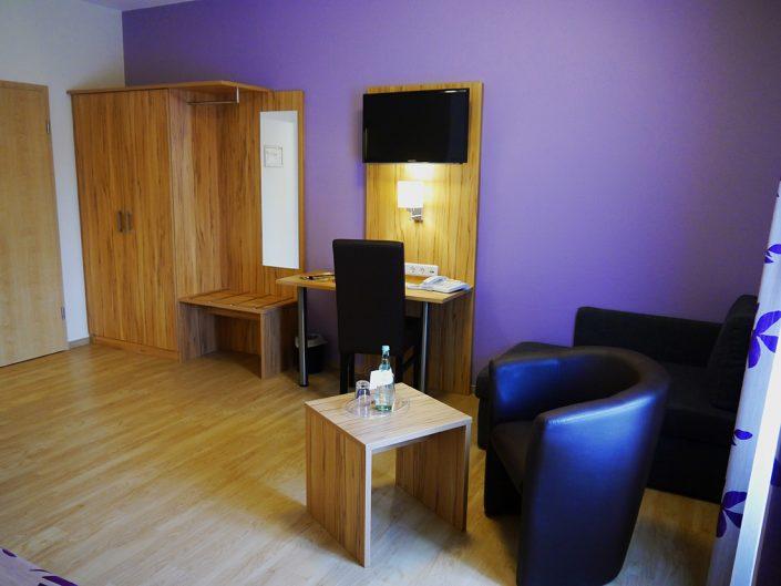 Hotel Room Purple Desk Television closet Water Bottle