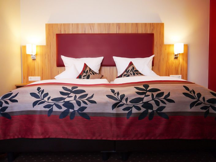 Hotel room bed pillow red lamps ceiling