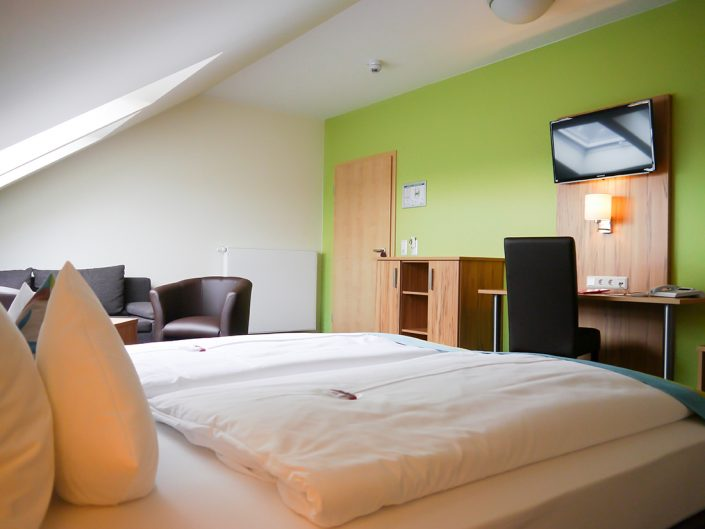 Hotel rooms Green Door, TV, bed, gummy bears, desk, chair